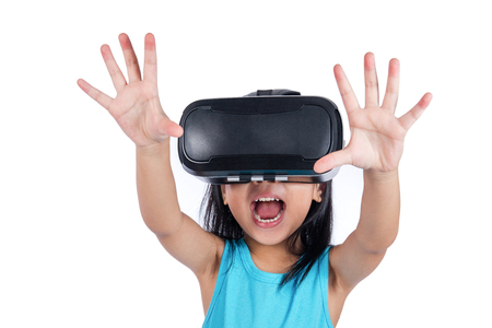 Asian little Chinese girl experiencing virtual reality via VR goggles in isolated white background Stock Photo