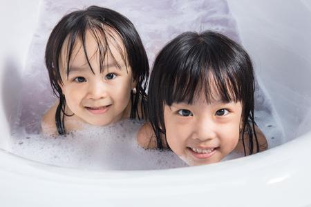 niñas chinas: Asia poco chicas chinas jugando con agua y espuma en la bañera en casa