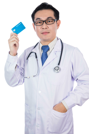 Asian Chinese male doctor holding credit card with stethoscope in isolated White Background