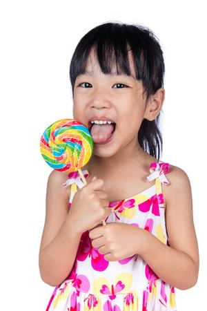 Aziaat Weinig Chinees meisje die lolly op geïsoleerde witte achtergrond eten