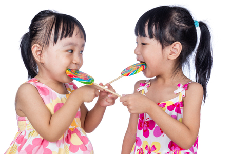 niñas chinas: Asian Little Chinese girls eating lollipop in isolated white background