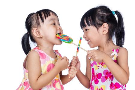 niñas chinas: Chicas asiáticas pequeñas chinas comiendo piruleta en fondo blanco aislado