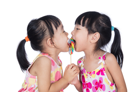 Asian Little Chinese girls eating lollipop in isolated white background