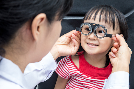Asian Little Chinese Girl Doing Eyes Examination by ophthalmologist at An Optical Shop Stock Photo