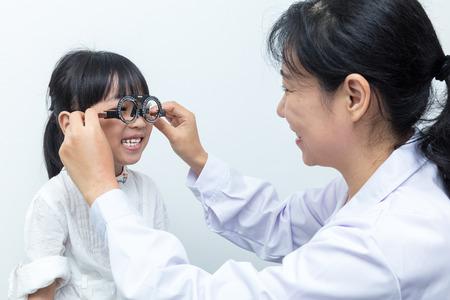 アジア少し中国少女やって目検査眼科医によって分離ホワイト バック グラウンドで