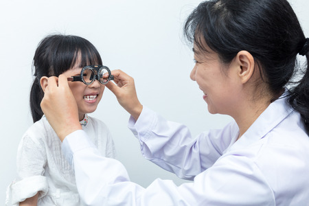 Asian Little Chinese Girl Doing Eyes Examination by ophthalmologist in isolated White Background