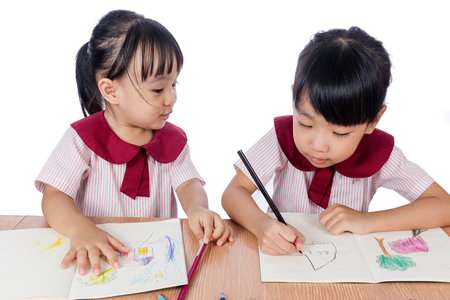 niñas chinas: Asian Little Chinese girls drawing with color pencils in isolated white background