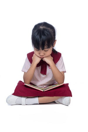 Asian Little Chinese girl in school uniform sitting on floor and reading book in isolated white background Stock Photo