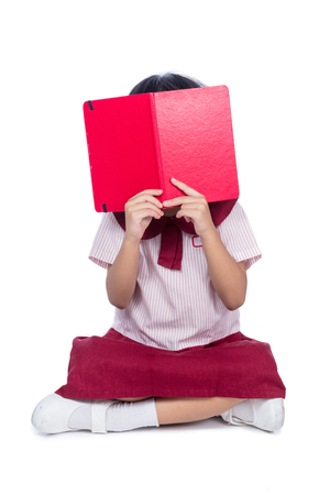 Asian Little Chinese girl in school uniform sitting on floor with book in isolated white background Stock Photo