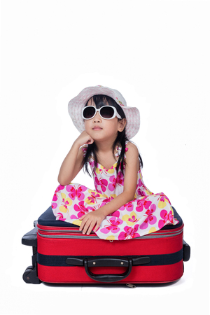 Happy Asian Little Chinese girl sitting on a suitcase in isolated white background Stock Photo