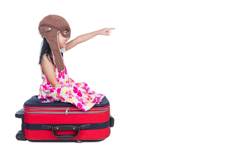 Happy Asian Little Chinese girl playing with a suitcase in isolated white background
