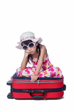 Asian Little Chinese girl sitting on a suitcase in isolated white background