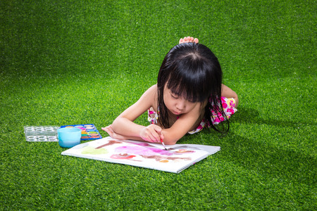 concentrate: Asian Chinese little girl lying on the grass drawing and painting
