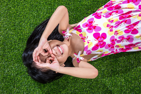 Asian Chinese little girl lying on the grass at outdoor park Stock Photo