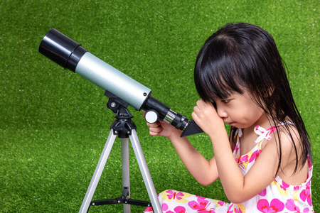 Asian Chinese little girl sitting on the grass and playing with a telescope