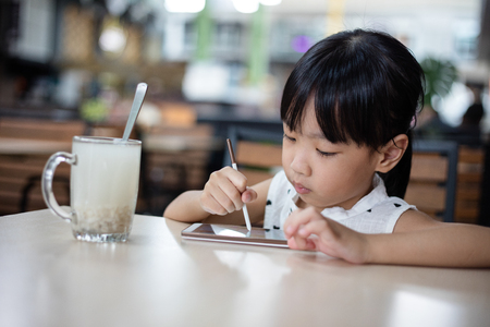 concentrate: Asian Chinese little girl playing smartphone at outdoor cafe Stock Photo