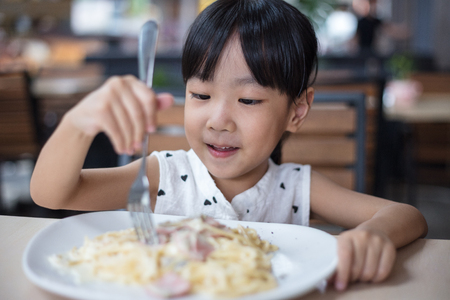 Asian Chinese little girl eating spaghetti at outdoor cafe Stock Photo