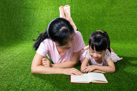 Asian Chinese mother and daughter lying on the grass and reading the book at outdoor park Фото со стока