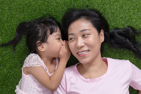 アジアの中国人の母とウィスパ リング ・屋外の公園で草の上に横たわる娘