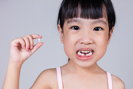 Asian Chinese little girl holding her missing tooth in isolated white background