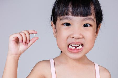 Asia Chino niña sosteniendo su diente perdido en fondo blanco aislado