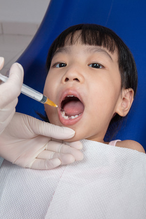 anaesthetic: Asian Chinese little girl lying down for tooth extraction at dental clinic Stock Photo