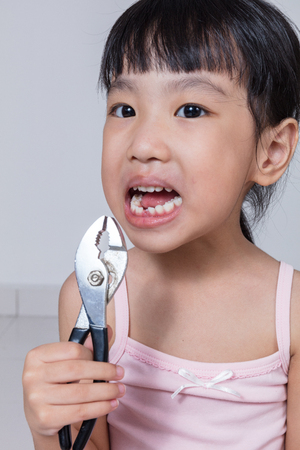 carious: Asian Chinese little girl holding pliers and showing the gap in isolated white background