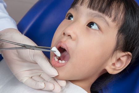 carious: Asian Chinese little girl lying down for tooth extraction at dental clinic Stock Photo