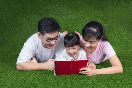 koncentrovaný: Asijské čínské rodiče a dcera ležící na trávě a čtení knihy ve venkovním parku
