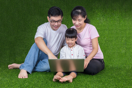 koncentrovaný: Asian Chinese parents and daughter sitting on the grass and playing laptop at outdoor park