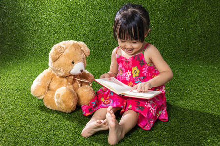 Asian Chinese little girl sitting on the grass and reading book with teddy bear at outdoor park