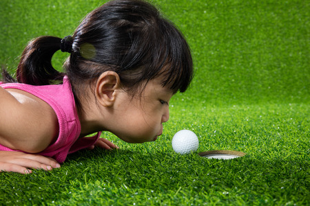 Asian Chinese little girl lying on grass and blowing the ball into a hole