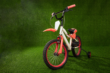 Kids bicycle parked on the green grass at outdoor park