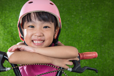 Asian Chinese little girl riding bicycle at outdoor park