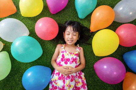 doze: Asian little Chinese girl lying on the grass amongst colorful balloons at outdoor park