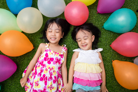 Asian little Chinese girls lying on the grass amongst colorful balloons at outdoor park Stock Photo