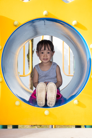 niños en recreo: Asian Chinese little girl sitting in the tunnel at outdoor playground