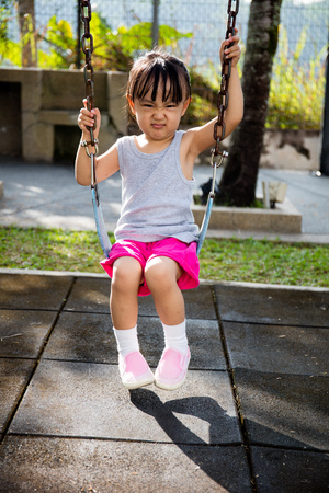 Asian little Chinese girl playing swing at outdoor park