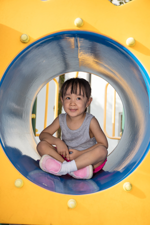 Asian Chinese little girl sitting in the tunnel at outdoor playground