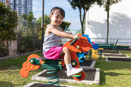 Asian Chinese little girl sitting on seesaw at outdoor playground