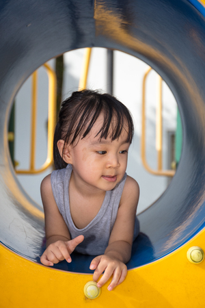 Asian Chinese little girl playing in the tunnel at outdoor playground Stock Photo