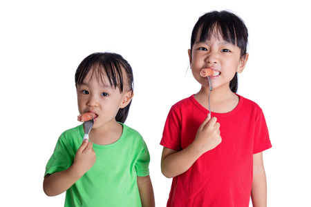 Asian Chinese little girls eating sausage in isolated white background Stock Photo