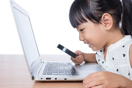 Asian Chinese little girl looking at laptop through magnifier in isolated white background