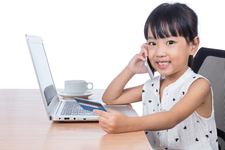 Asian Chinese little girl making online payment in isolated white background