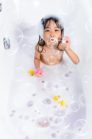 Asian little Chinese girl blowing bubbles in bathtub at home