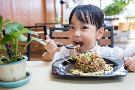 Asian Chinese little girl eating fried rice at outdoor cafe Stock Photo - 82367171