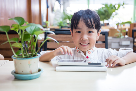 resting: Asian Chinese little girl playing tablet computer at outdoor cafe Stock Photo