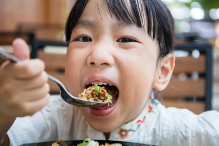 Asian Chinese little girl eating fried rice at outdoor cafe