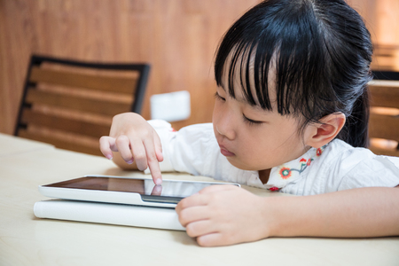 Asian Chinese little girl playing tablet computer at outdoor cafe Stock Photo