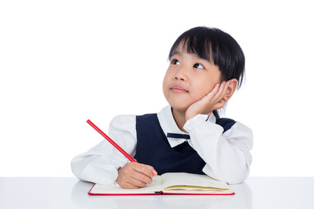 Asian Little Chinese girl writing homework in isolated white background 스톡 콘텐츠